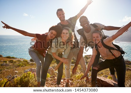 Millennial friends on a hiking trip reach the summit and have fun posing for photos #1454373080