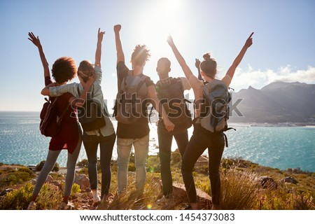 Millennial friends on a hiking trip celebrate reaching the summit and admire the view, back view #1454373083