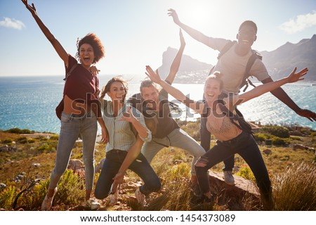 Millennial friends on a hiking trip reach the summit and have fun posing for photos #1454373089