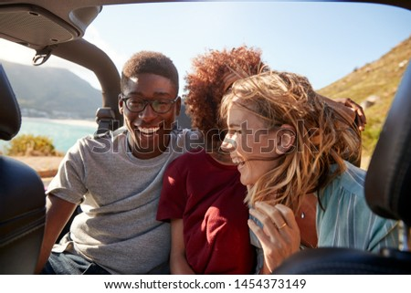 Three happy young adult friends sitting in an open car by the coast, close up, waist up #1454373149