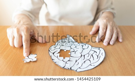 Elderly woman hands putting missing white jigsaw puzzle piece down into the place as a human brain shape. Creative idea for memory loss, dementia, Alzheimer's disease and mental health concept. #1454425109