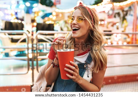 Image of blonde charming woman wearing girlish clothes drinking soda beverage from paper cup while walking in amusement park Royalty-Free Stock Photo #1454431235