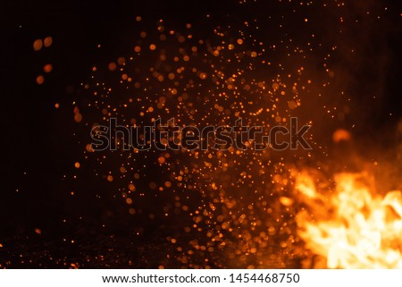 Burning red hot sparks fly from big fire. Beautiful abstract background on the theme of fire. Burning coals, flaming particles flying off against black background.