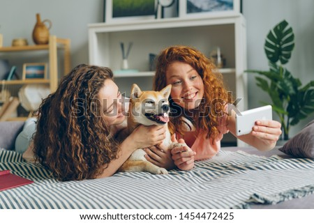 Siblings beautiful girls are taking selfie with cute puppy lying on couch at home using smartphone camera. Modern technology, people and animals concept.