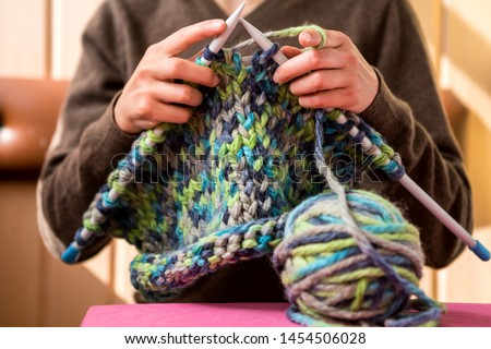 A woman knits from thick yarn. Handmade clothes. The girl sits on the couch and goes in for her hobbies. Knitting close up. Royalty-Free Stock Photo #1454506028