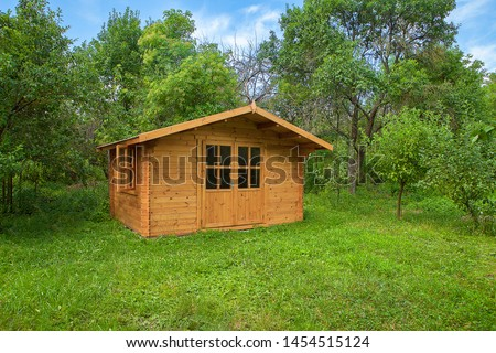 Garden shed. Gardening tools shed. Garden house on lawn in garden. Wooden tool-shed. Hovel made of timber.  #1454515124