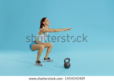Squats. Fitness woman in sports wear exercising, doing squat workout at studio. Full length portrait of fit girl squatting on blue background #1454545409