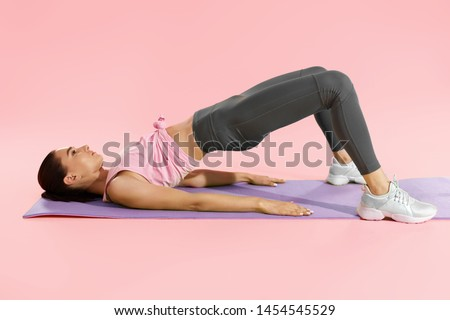 Fitness woman doing hip workout exercise on yoga mat at studio. Full length shot of fit girl model in sportswear exercising, doing pelvic muscle exercises on pink background #1454545529