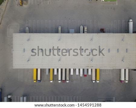 Aerial view of goods warehouse. Logistics center in industrial city zone from above. Aerial view of trucks loading at logistic center. View from drone. #1454591288