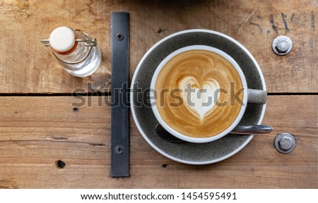 a cup of cappuccino with latte art with syrup on wooden background. Black ceramic cups top view closeup, place for text #1454595491