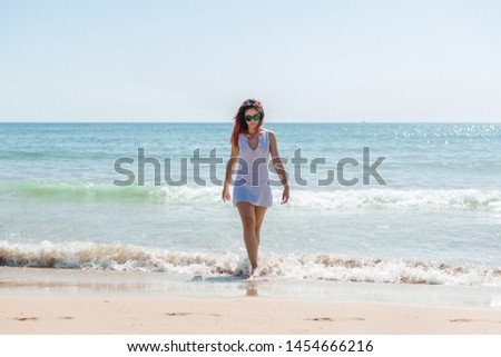 Young woman walks on the beach in a white dress. Lifestyle, summer. #1454666216