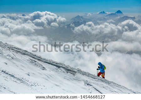 man climbs uphill on a background of clouds #1454668127