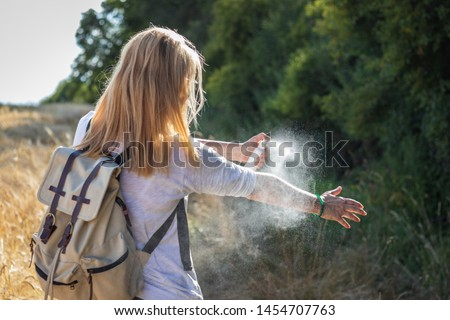 Woman tourist applying mosquito repellent on hand during hike in nature. Insect repellent. Skin protection against tick and other insect.  #1454707763