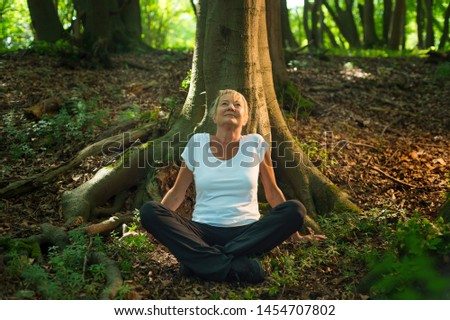 Experience the forest while bathing in the forest (Shinrin Yoku) with all her senses. A 50 year old blonde woman sits cross legged relaxed. She feels the sun and the atmosphere of the deciduous forest #1454707802