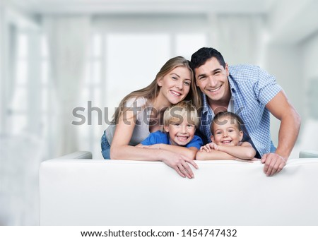 Beautiful smiling family in room on couch #1454747432