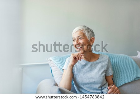 Happy woman relaxing on her couch at home in the sitting room. Portrait of beautiful mature woman smiling while sitting at sofa at home. Beautiful middle age woman smiling at home #1454763842