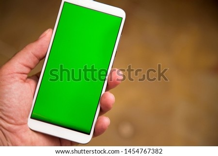 Left handed man hand touching the smart phone with green chroma screen.
