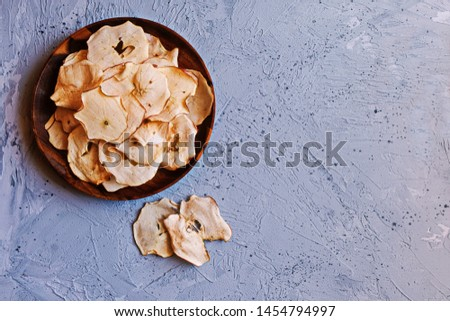 Chips of fresh apples with cinnamon on a plate on on a blue background. Organic apple chips. Dried fruits. Healthy sweet snack. Dehydrated and raw food. Copy space. Top view #1454794997