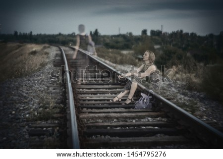 Lonely sad girl sitting on the rails of the railway and smokes, then goes into the distance.Toned photo. Double exposure. Concept: depression, neschastna love, separation, personality psychology.