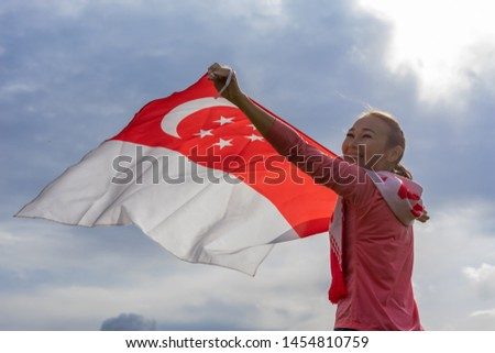 Singapore flag waving on wind on cloudy sky background. Singapore Flag Day. Young joyful woman holds Flag of Singapore fluttering in sunny rays high. Holiday,  National Day of Singapore Concept. #1454810759