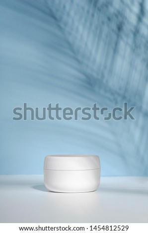 A white jar of cream on a stand on a blue background, on a white table with tropical palm leaves and their shadow. Stylish look of the product, mock up, identity. #1454812529