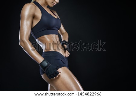 Athletic woman with strong abdominal muscles posing with her hands on her hips with copy space. Attractive muscular woman with gloved hands on strong abs. Muscular pumped woman after workout. #1454822966