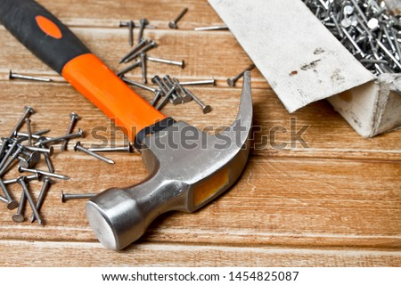 Hammer and nails scattered on wooden background. Joinery concept #1454825087