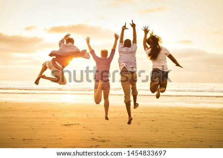 group of happy young people dancing on the beach Royalty-Free Stock Photo #1454833697