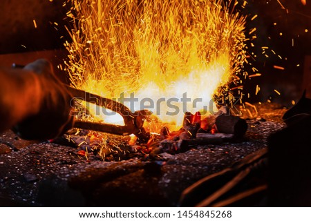 Unrecognizable Hands of Smith Preparing Metal on Anvil for Forging with spark fireworks Royalty-Free Stock Photo #1454845268