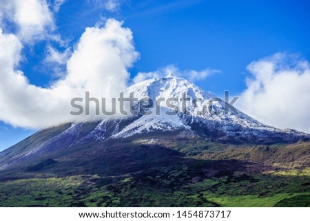 Mount Pico volcano summit covered in snow under blue sky and clouds, in Azores, Portugal. #1454873717