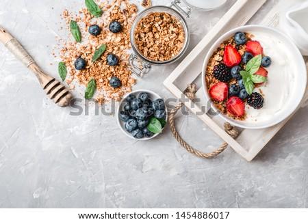 Healthy breakfast with granola, yogurt, fruits, berries on white background. #1454886017