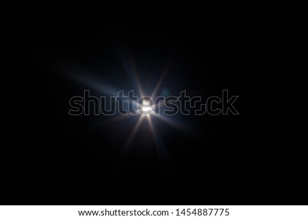 Lens Flare. Light over black background. Easy to add overlay or screen filter over photos. Abstract sun burst with digital lens flare background. Gleams rounded and hexagonal shapes, rainbow halo. Royalty-Free Stock Photo #1454887775