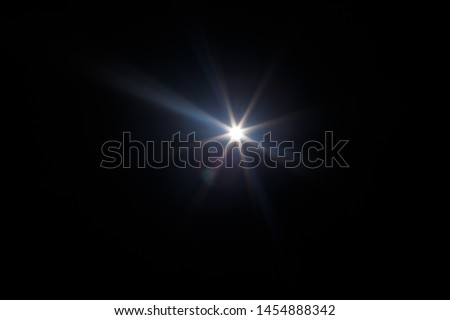 Lens Flare. Light over black background. Easy to add overlay or screen filter over photos. Abstract sun burst with digital lens flare background. Gleams rounded and hexagonal shapes, rainbow halo. #1454888342