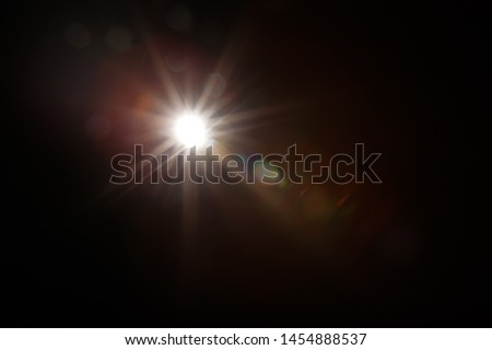 Lens Flare. Light over black background. Easy to add overlay or screen filter over photos. Abstract sun burst with digital lens flare background. Gleams rounded and hexagonal shapes, rainbow halo. #1454888537