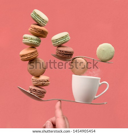 Perfect balance concept still life on coral color paper backgound. Balancing cup of coffee and macarons on a finger. #1454905454