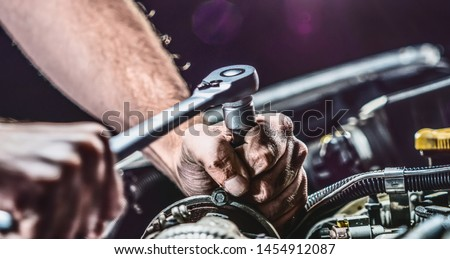 Auto mechanic working on car engine in mechanics garage. Repair service. authentic close-up shot Royalty-Free Stock Photo #1454912087