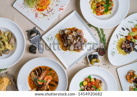 Assorted foodset of European food on table. Seafood casserole bowl, file minion with truffle, vongole, salad with octopus, salad with shrimps