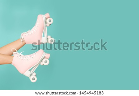 Pink roller skates on the legs. Activity can be fun!