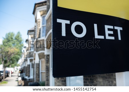 Estate agent 'TO LET' sign on street of typical British street