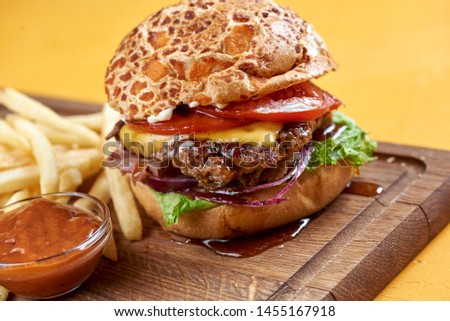 burger with onion rings, cheese and jack daniel's sauce
