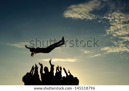 Group throwing girl in the air Royalty-Free Stock Photo #145518796
