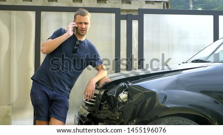 car accident concept. man in a state of shock talking on the phone after a car accident, standing by a car with a broken bumper #1455196076