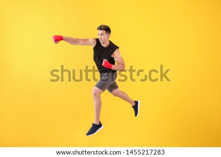 Sporty male kickboxer on color background #1455217283