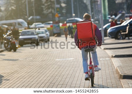 Young boy on bicycle delivering food in boxes with red thermal bag. Pizza delivery cyclist carries isothermal backpack. Food delivery in any weather around the clock. Food delivery or takeout #1455242855
