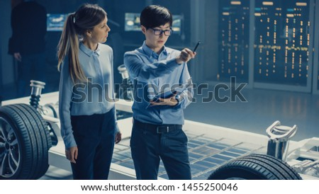 Male and Female Automobile Design Electric Car Engineers Having Conversation, Use Clipboard to Check Maintenance Issues. Innovative Hybrid Vehicle Platform Chassis Concept with Wheels, Engine, Battery #1455250046