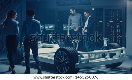 Team of Automotive Engineers Discussing and Designing Electric Car Platform Chassis Prototype, Taking Measures, Working with 3D CAD Software, Checking Quality Control. Vehicle Frame with Wheels #1455250076