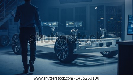 Automobile Engineer Enter Automotive Innovation Facility to Work on Electric Car Chassis Platform, Using Augmented Reality with 3D CAD Software Modelling. Innovative Facility: Vehicle Frame with Wheel #1455250100