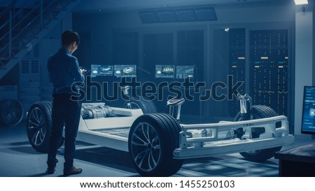 Automobile Engineer Working on Electric Car Chassis Platform, Using Tablet Computer Augmented Reality with 3D CAD Software Modelling. Innovative Facility: Vehicle Frame with Wheels, Engine, Battery Royalty-Free Stock Photo #1455250103
