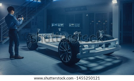 Automobile Engineer Working on Electric Car Chassis Platform, Using Tablet Computer Augmented Reality with 3D CAD Software Modelling. Innovative Facility: Vehicle Frame with Wheels, Engine, Battery #1455250121