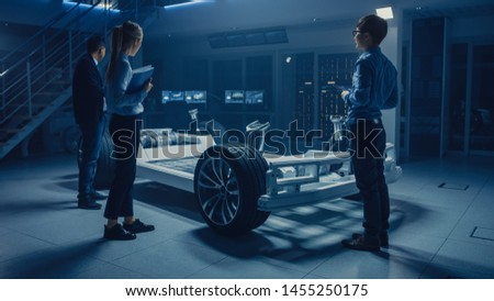 Automobile Engineers Working on Electric Car Platform Chassis, Using Tablet Computers with CAD Software for 3D Concept. In Automotive Innovation Facility Vehicle Frame with Wheels, Engine and Battery #1455250175